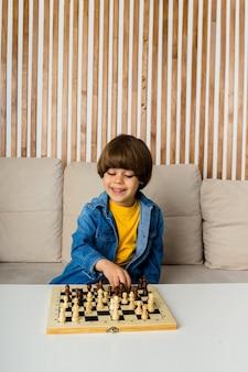 Glücklicher kleiner kaukasischer junge mit braunen haaren sitzt auf einem sofa und spielt schach. entwicklung des kindes
