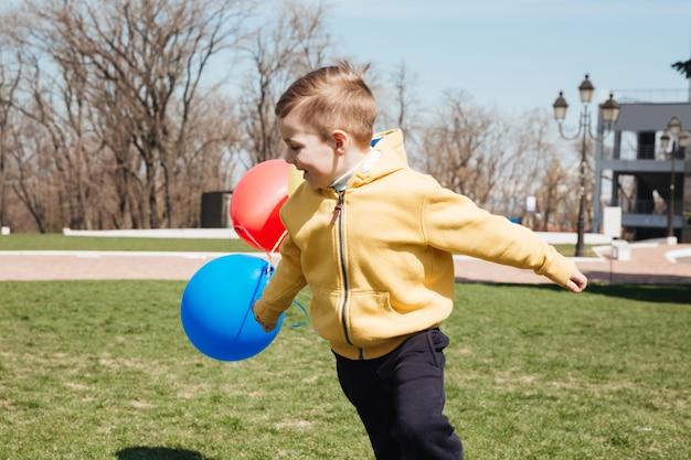Glücklicher kleiner kinderjunge, der draußen im park mit luftballons geht