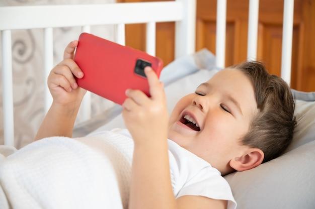 Glücklicher kleiner kleinkindjunge, der mit einem smartphone auf dem bett spielt. konzept der internet-abhängigkeit. foto in hoher qualität