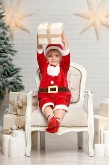 Glücklicher kleiner lächelnder junge in weihnachtsmann-kostüm, das auf lehnsessel nahe weihnachtsbaum sitzt und weihnachtsgeschenkbox hält
