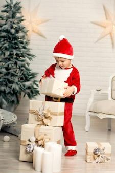 Glücklicher kleiner lächelnder junge in weihnachtsmann-kostüm hält geschenkbox der weißen weihnacht