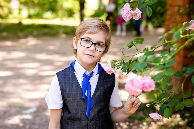 Glücklicher kleiner schüler mit gläsern und blauer bindung