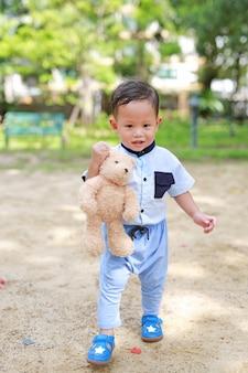 Glücklicher kleinkindjunge, der draußen mit dem halten des teddybären im park geht.