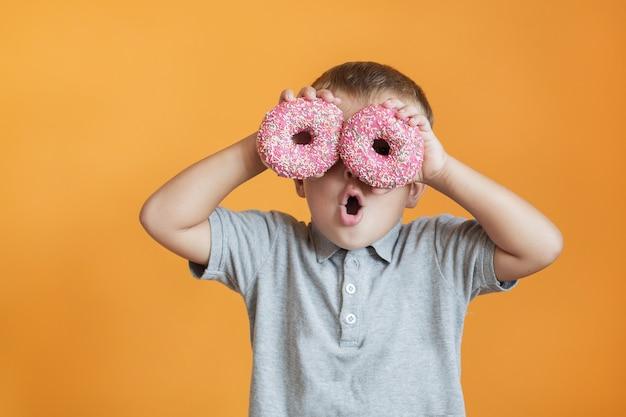 Glücklicher kleinkindjunge mit zwei donuts nahe seinen augen
