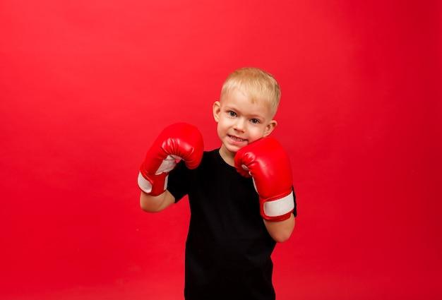 Glücklicher kleinkindjungenboxer in den roten boxhandschuhen an der roten wand