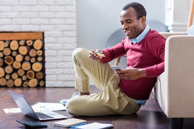 Glücklicher kluger netter mann, der sein smartphone hält und die kreditkarte beim online-bezahlen betrachtet