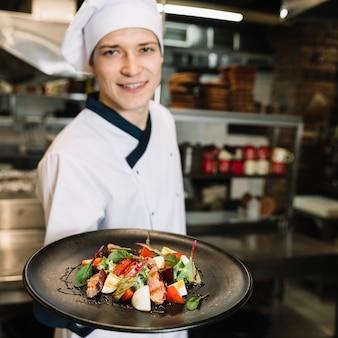Glücklicher koch, der salat mit fleisch auf platte zeigt