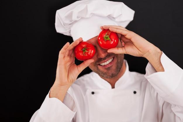 Glücklicher koch, der seine augen der tomaten bedeckt