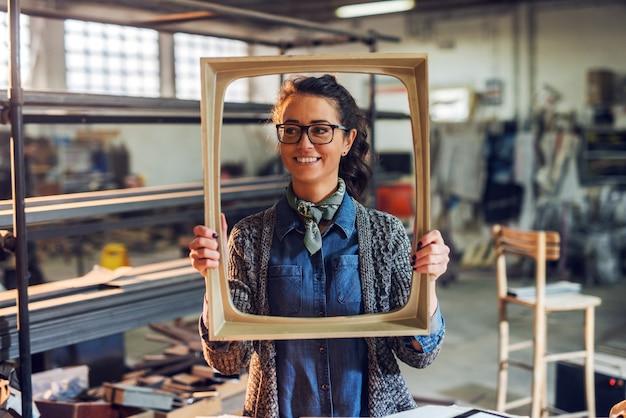 Glücklicher kreativer weiblicher zimmermann des mittleren alters, der bilderrahmen vor ihrem gesicht hält. stehend in ihrer werkstatt.