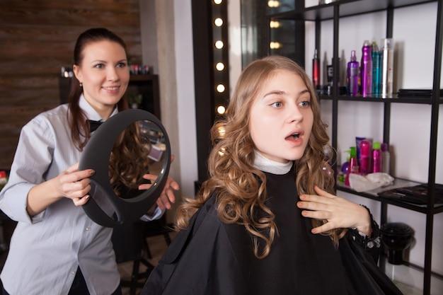 Glücklicher kunde, der spiegel im salon betrachtet. stylistin steht hinter dem stuhl