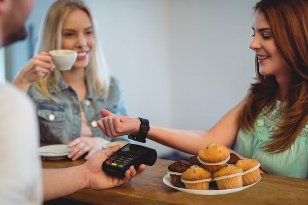 Glücklicher kunde mit der intelligenten uhr, die am café zahlt