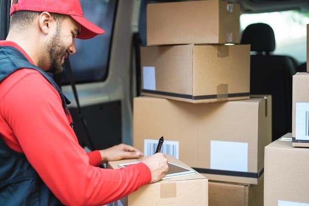 Glücklicher kuriermann, der paketzustellung im lieferwagen unterschreibt - fokus auf gesicht