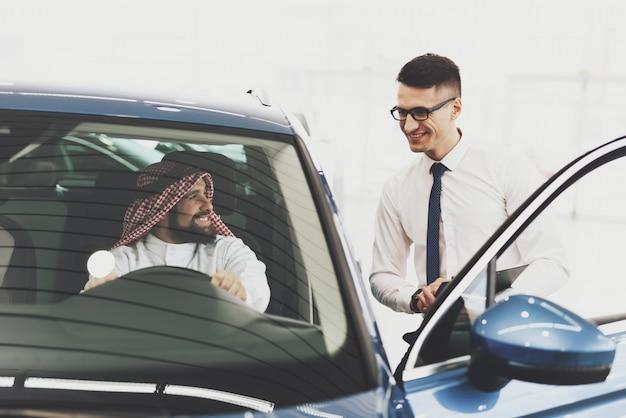 Glücklicher kuwaitischer mann und autohändler im ausstellungsraum.