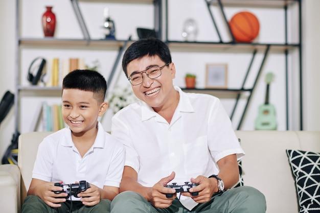 Glücklicher lachender asiatischer mann, der videospiel mit seinem sohn am wochenende spielt