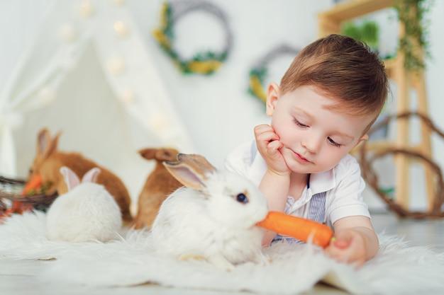 Glücklicher lachender kleiner junge, der mit einem babykaninchen spielt