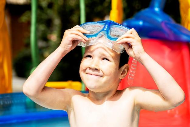Glücklicher lachender kleinkindjunge, der spaß in einem schwimmbad hat