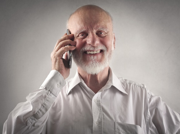 Glücklicher lächelnder älterer mann, der am telefon spricht