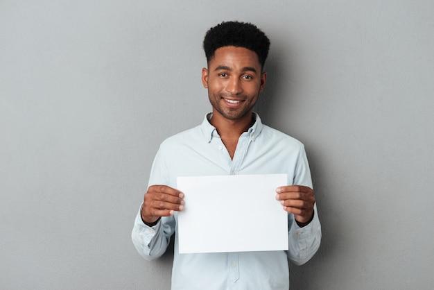 Glücklicher lächelnder afrikanischer mann, der leeres blatt papier hält