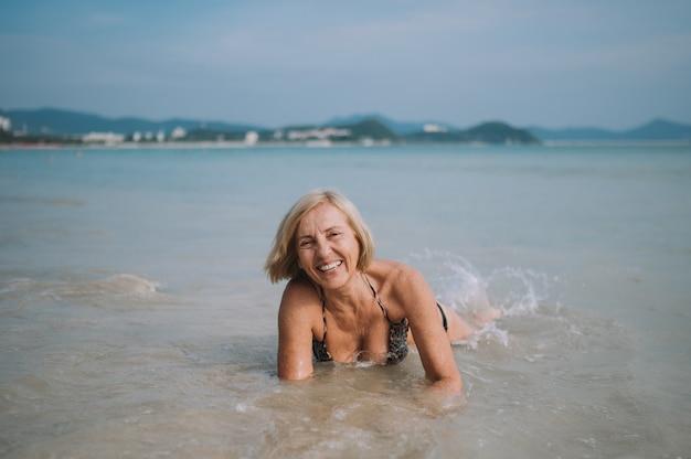 Glücklicher lächelnder aufgeregter älterer älterer frauentourist, der im wasser spielt und in den großen wellen auf dem ozeanseestrand schwimmt. reisen entlang asiens, aktives lifestyle-konzept.