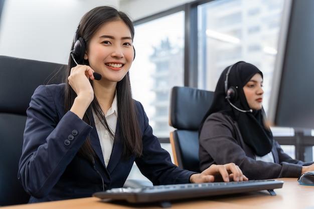 Glücklicher lächelnder betreiber asiatischer frau-kundendienstmitarbeiter mit headsets, die am computer in einem callcenter arbeiten und mit dem kunden sprechen, um zu helfen, das problem mit ihrem service-verstand zu lösen
