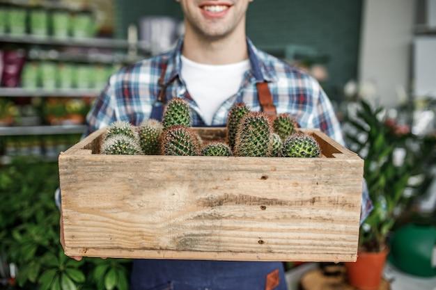 Glücklicher lächelnder gärtner, der topf mit kaktus in einem blumenladen hält