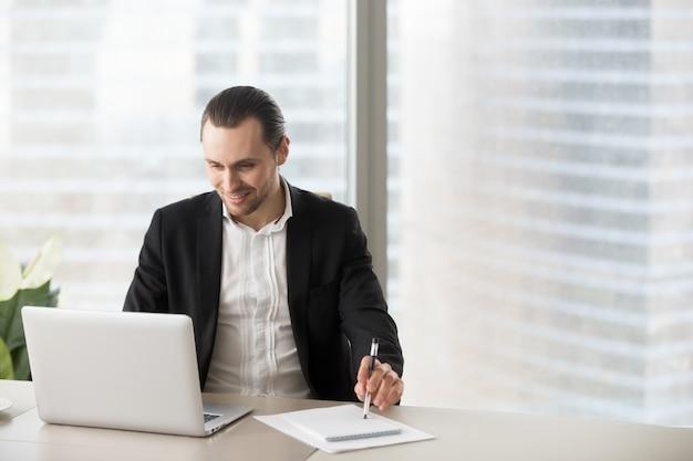 Glücklicher lächelnder geschäftsmann im büro, das laptop sreen betrachtet.