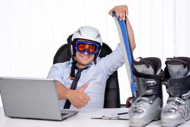 Glücklicher lächelnder geschäftsmann im ski dörfchen und in der maske.