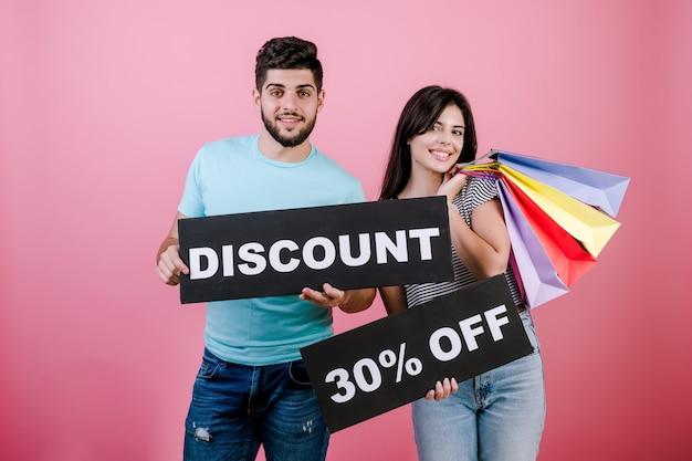 Glücklicher lächelnder gutaussehender paarmann und -frau mit rabatt 30% weg vom zeichen und von den bunten einkaufstaschen