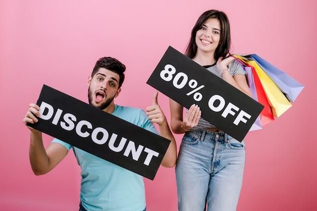 Glücklicher lächelnder gutaussehender paarmann und -frau mit rabatt 90% weg vom zeichen und von den bunten einkaufstaschen