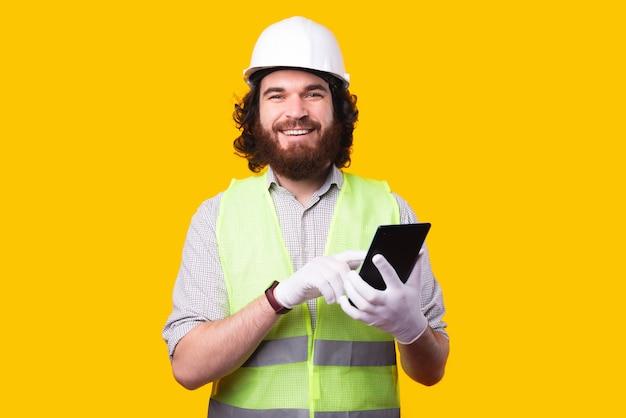 Glücklicher lächelnder ingenieurmann, der schutzhelm trägt und tablette verwendet