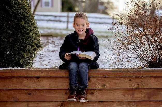 Glücklicher lächelnder junge, der auf einem hölzernen zaun sitzt und ein buch in einem park liest