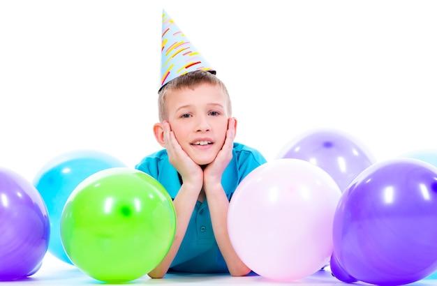 Glücklicher lächelnder junge im blauen t-shirt, das auf dem boden mit bunten luftballons liegt und daumen hoch zeigt - lokalisiert auf einem weiß