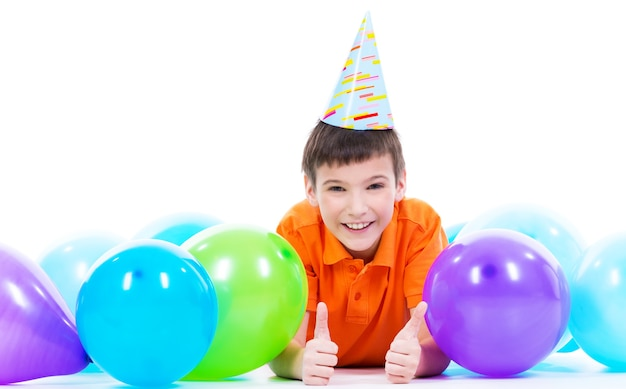 Glücklicher lächelnder junge im orangefarbenen t-shirt, das auf dem boden mit bunten luftballons liegt und daumen hoch zeigt - lokalisiert auf einem weiß