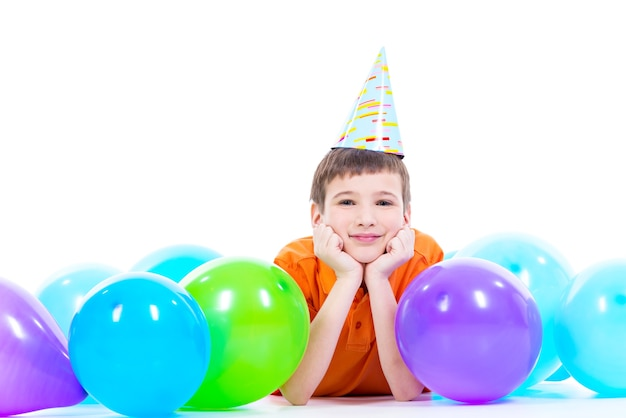 Glücklicher lächelnder junge im orangefarbenen t-shirt, das auf dem boden mit bunten luftballons liegt und daumen hoch zeigt - lokalisiert auf einem weiß Kostenlose Fotos