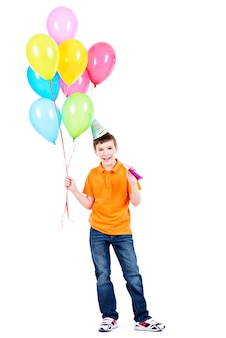 Glücklicher lächelnder junge im orangefarbenen t-shirt, das bunte luftballons hält - lokalisiert auf einem weiß