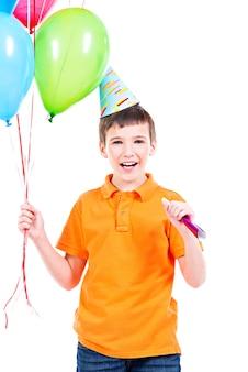 Glücklicher lächelnder junge im orangefarbenen t-shirt, das bunte luftballons hält - lokalisiert auf einem weiß.