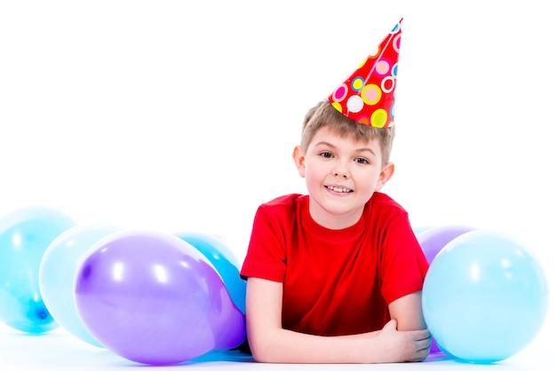 Glücklicher lächelnder junge im roten t-shirt, das auf dem boden mit bunten luftballons liegt - lokalisiert auf einem weiß.