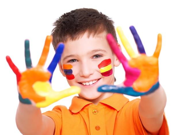 Glücklicher lächelnder junge mit gemalten händen und gesicht im orange t-shirt - auf einem weißen raum.