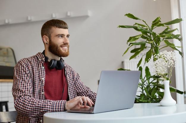 Glücklicher lächelnder junger attraktiver bärtiger mann des ingwers sitzt an einem tisch in einem café und arbeitet an einem laptop, trägt in der grundkleidung, schaut weg.