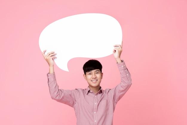Glücklicher lächelnder junger hübscher asiatischer mann, der spracheblase hält