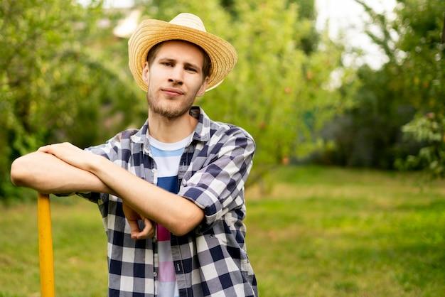 Glücklicher lächelnder junger hübscher landarbeiter mit bart mit gartenwerkzeugen protrait a