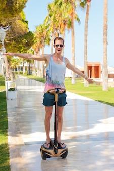 Glücklicher lächelnder junger mann auf segway. reitengyroscooter auf einer sonnigen sommerpalmengasse