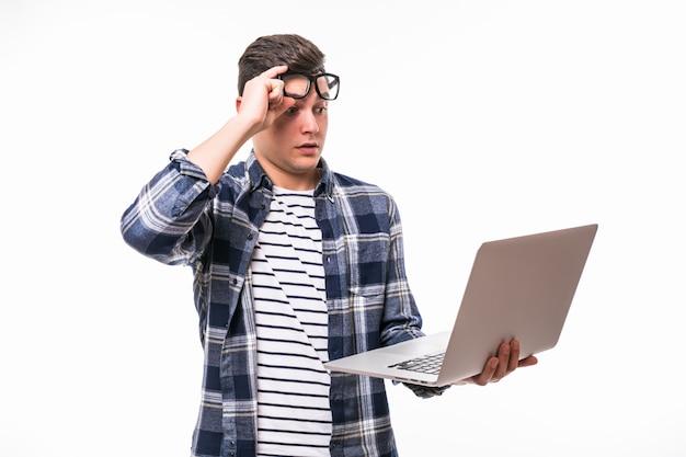 Glücklicher lächelnder junger mann, der computer beobachtet und arbeitet