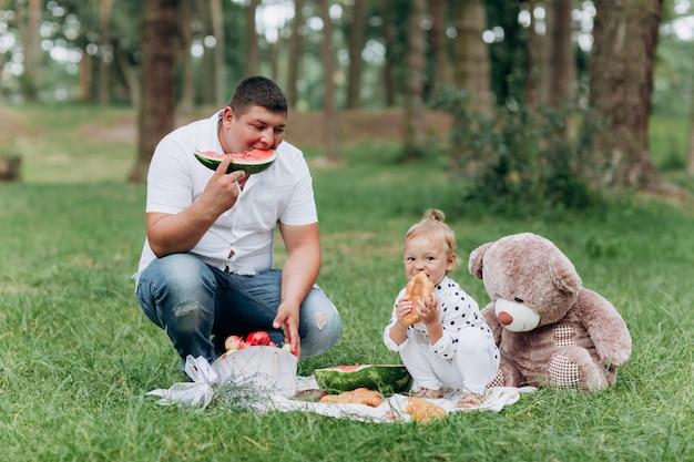 Glücklicher lächelnder junger vater und tochter auf picknick im park am sommertag. das konzept der sommerferien. vatertag, babytag. zeit zusammen verbringen. selektiver fokus.