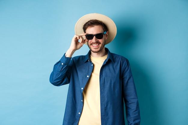Glücklicher lächelnder kerl, der auf sommerferien geht, strohhut und schwarze sonnenbrille tragend, auf blauem hintergrund stehend.