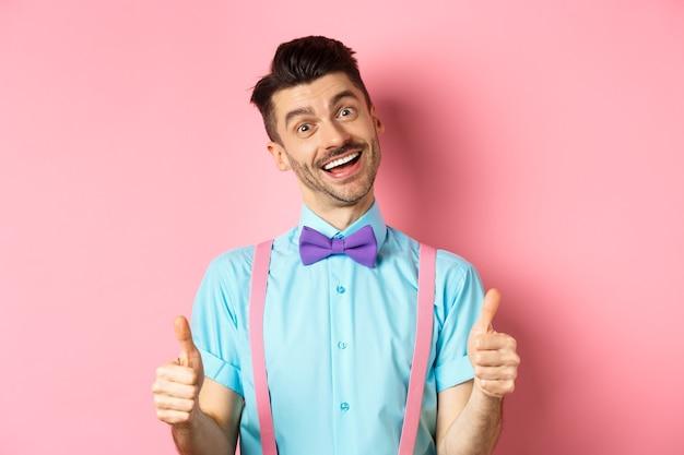 Glücklicher lächelnder kerl in der fliege und in den hosenträgern, die daumen hoch zeigen, guten job loben, nette arbeit genehmigen, zufrieden über rosa hintergrund stehen.