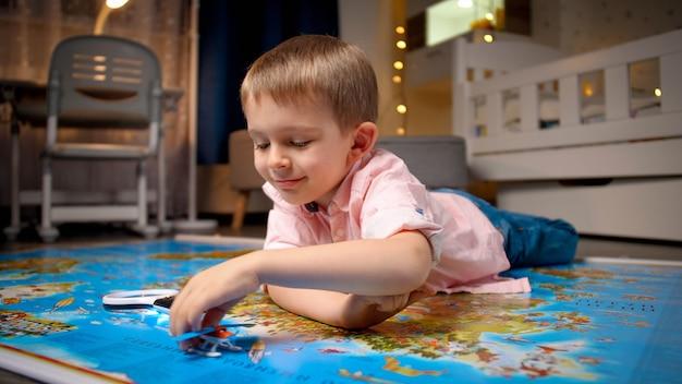 Glücklicher lächelnder kleiner junge, der auf großer karte liegt und mit spielzeugflugzeug spielt. konzept von reisen, tourismus und kindererziehung. kinder erkunden und entdecken.