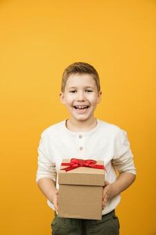 Glücklicher lächelnder kleiner junge, der geschenkbox mit rotem band und herzform lokalisiert, kind gibt geschenk, banner.