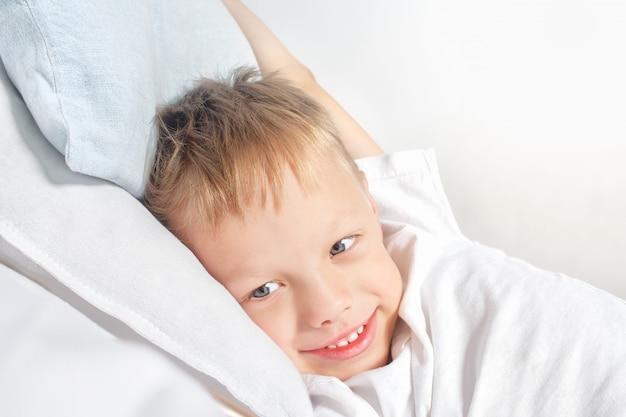 Glücklicher lächelnder kleiner junge, nachdem das ausdehnen in bett aufgewacht ist. guten morgen . porträt eines weißen kindes mit grauen augen und dem blonden haar das leben zu hause genießend.