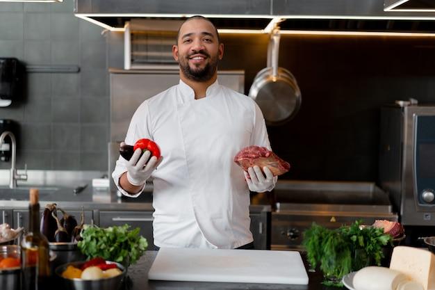 Glücklicher lächelnder koch bereitet fleischgericht mit verschiedenem gemüse in der küche zu. in der einen hand hält der mann gemüse, in der anderen ein stück frisches fleisch